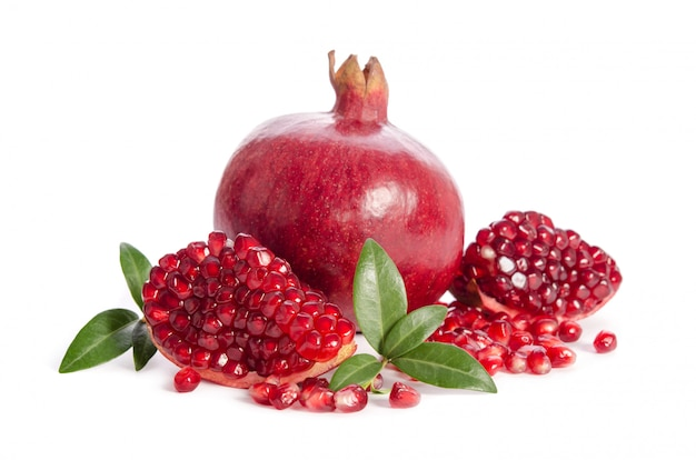 Ein ganzer und ein teil eines granatapfels mit den granatapfelsamen und -blättern lokalisiert auf weiß