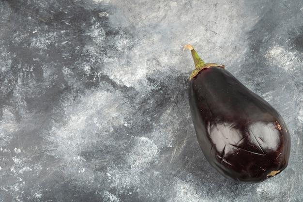 Ein ganzes auberginengemüse auf einen marmortisch gelegt.