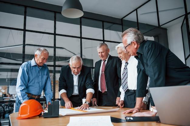 Ein gealtertes team älterer geschäftsmannarchitekten arbeitet mit plan im büro.