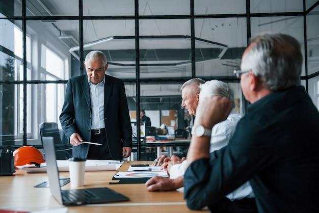 Ein gealtertes team älterer geschäftsmannarchitekten trifft sich im büro.