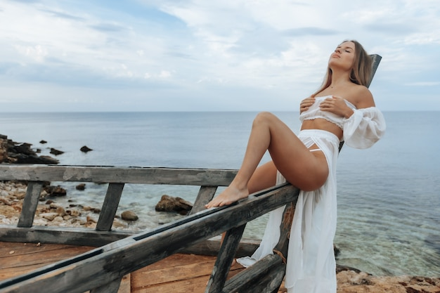 Ein gebräuntes mädchen in einem sexy weißen kleid sitzt auf dem bug eines zerstörten schiffes am strand