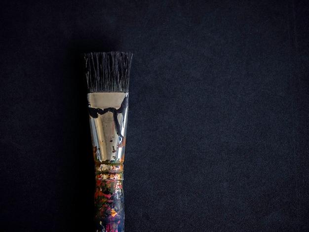 Ein gebrauchter künstlerpinsel isoliert auf dunkler oberfläche