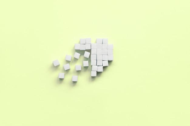 Ein gebrochenes herz aus zuckerwürfeln liegt auf einem trendigen pastellkalk