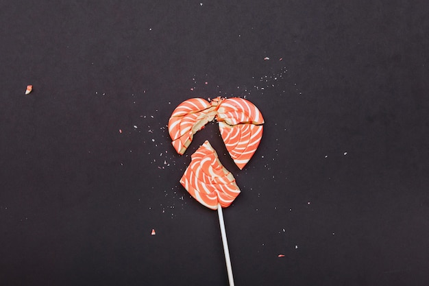Ein gebrochenes karamellherz liegt auf einem dunkelgrauen hintergrund. valentinstag fehlgeschlagen.