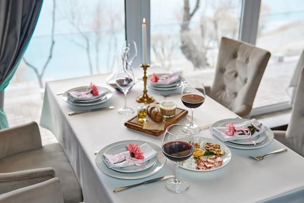 Ein gedeckter restauranttisch mit gläsern rotwein und vorspeise erwartet die gäste