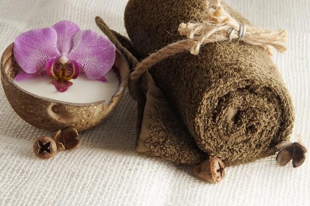 Ein gefaltetes handtuch, gebunden mit einem seil und einer orchideenblüte in milch in einer kokosnuss auf einer leicht gewebten serviette, bereitet das spa-verfahren vor.