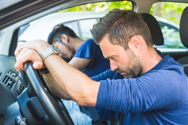 Ein gelangweilter mann im auto blieb im verkehr stecken