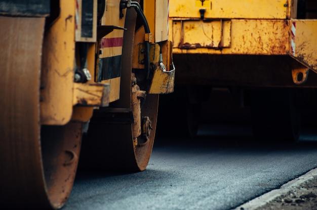 Ein gelber asphaltverdichter richtet die straße aus. neuen asphalt verlegen.