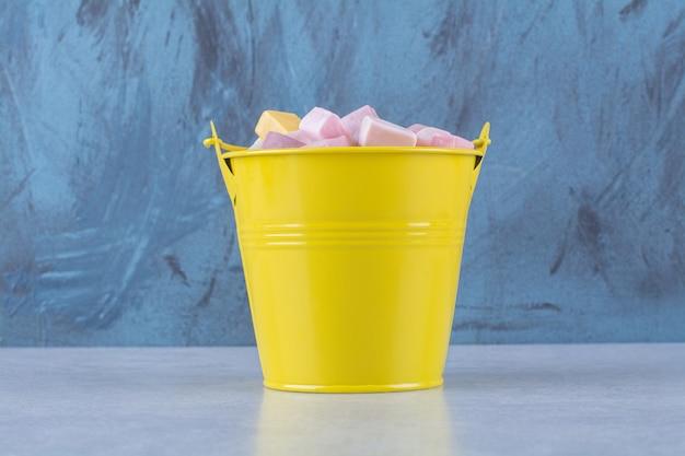 Ein gelber eimer mit rosa und gelben süßen süßwaren pastila