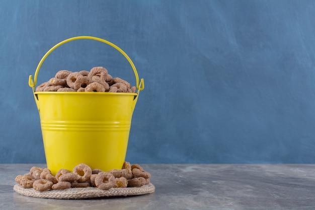 Ein gelber eimer voller gesundes leckeres getreide auf sackleinen.