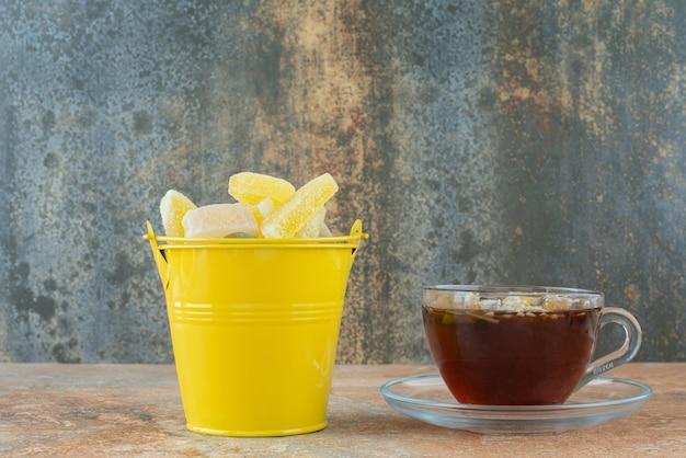 Ein gelber eimer voller zuckergelee-bonbons und einer tasse kräutertee