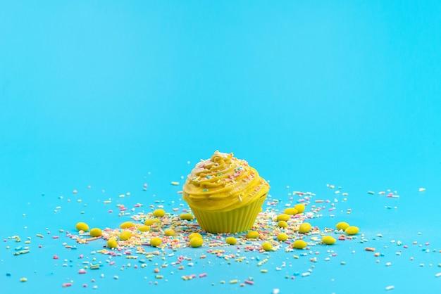 Ein gelber kuchen der vorderansicht mit bunten kleinen bonbonpartikeln auf blauem schreibtisch, süßer keks des kuchens