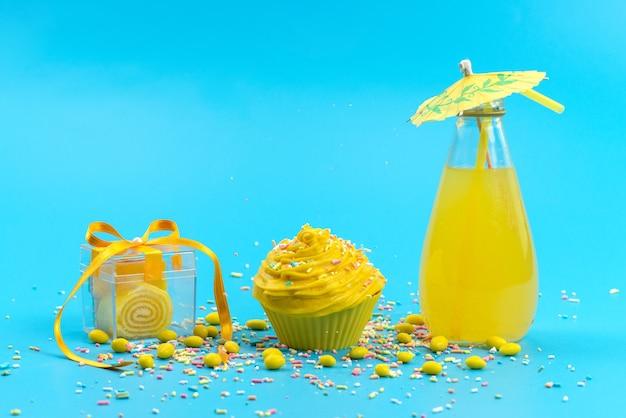 Ein gelber kuchen der vorderansicht mit süßigkeiten und frischem zitronensaft auf blauem schreibtisch, süße farbe des kuchenkekses