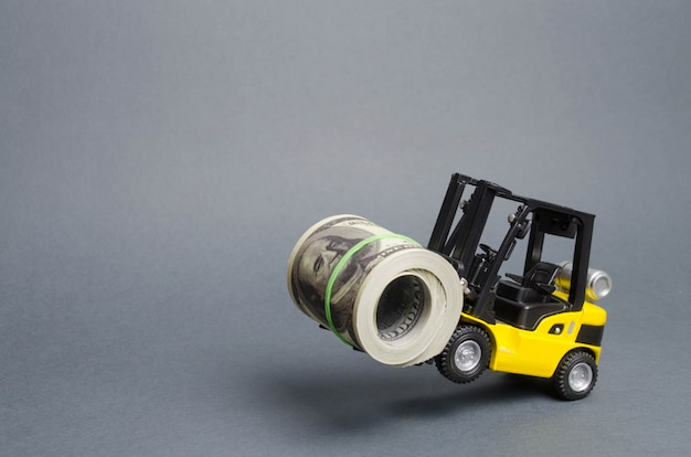 Ein gelber lader steht auf den hinterrädern und hält ein großes bündel dollar. konzept der investition