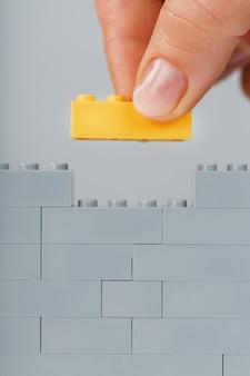 Ein gelber ziegelstein legt eine hand auf eine graue spielzeugwand