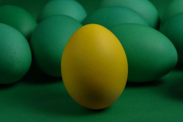 Ein gelbes gemaltes osterei steht vor grünen eiern auf einem grünen hintergrund.