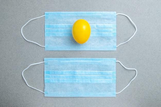 Ein gelbes osterei liegt auf einer blauen medizinischen maske auf einem grauen tisch.