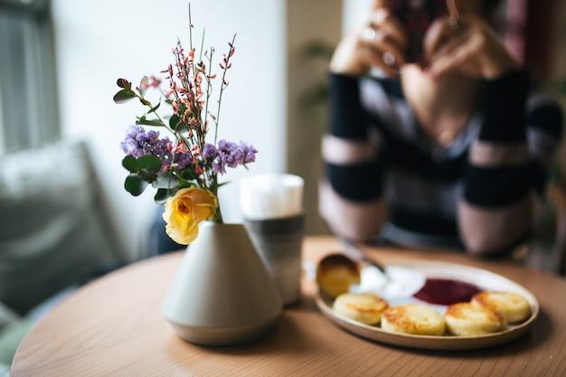 Ein gemütliches frühstück in hellen farben. vase mit blumen, käsekuchen