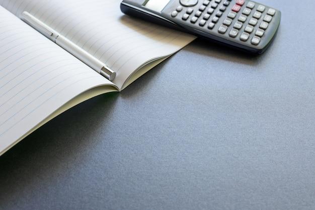 Ein geöffnetes notizbuch mit einem stift und einem taschenrechner, auf dunkelgrauem hintergrund, szene schule oder büro.