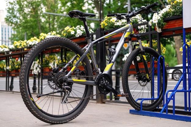 Ein geparktes fahrrad auf einer straße in der nähe einer straße, blumen
