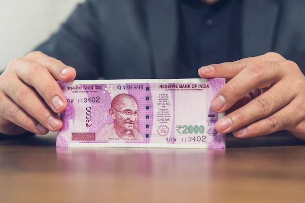 Ein geschäftsmann an einem finanzinstitut, das banknoten der indischen rupie zählt und anzeigt