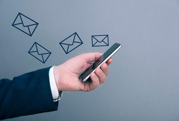 Ein geschäftsmann bekommt viele neue nachrichten, e-mail an das telefon. mann hält telefon. geschäftskonzept bild.