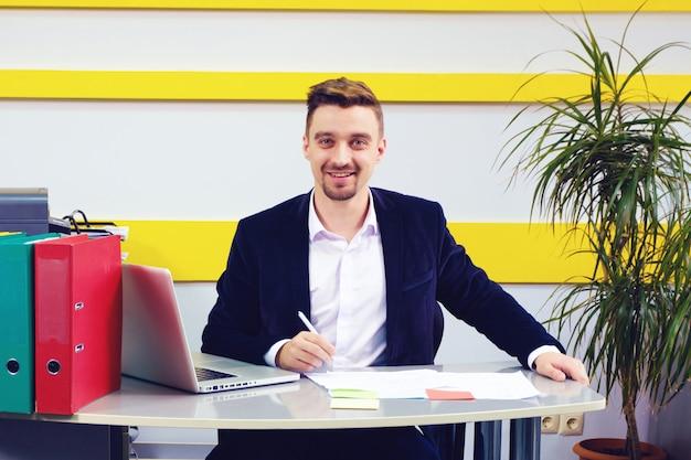 Ein geschäftsmann, der am arbeitsplatz lächelt