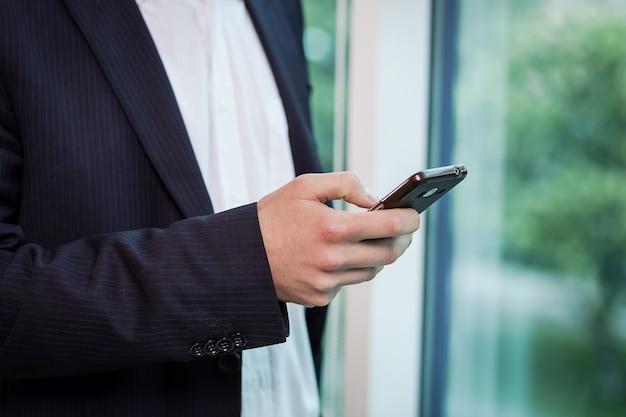 Ein geschäftsmann, der auf einem mobiltelefon spricht, geschäftsmann, der am telefon im büro spricht, älterer geschäftsmann, porträt des geschäftsmanns, der auf mobiltelefon spricht, geschäftskonzept