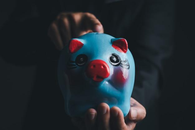 Ein geschäftsmann, der das blaue sparschwein hält, nahaufnahme mit kopienraum für individuellen text, spar- und investitionskonzept