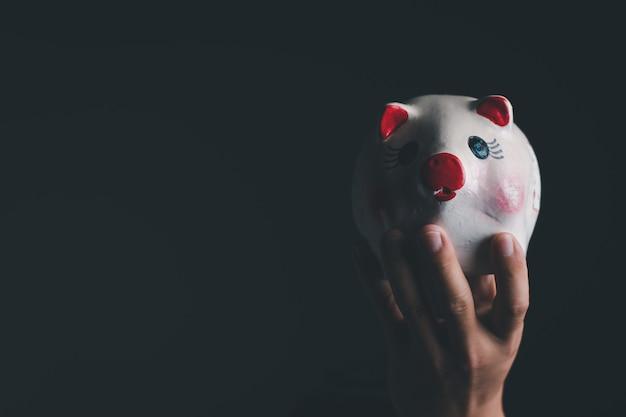 Ein geschäftsmann, der das weiße sparschwein hält, nahaufnahme mit kopienraum für individuellen text, spar- und investitionskonzept
