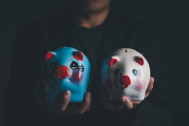 Ein geschäftsmann, der das weiße und blaue sparschwein hält, nahaufnahme mit kopienraum für individuellen text, spar- und investitionskonzept