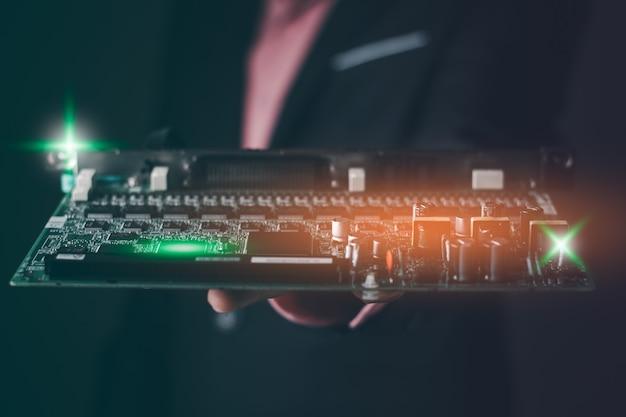 Ein geschäftsmann, der den elektronischen chip des grünen brettes hält