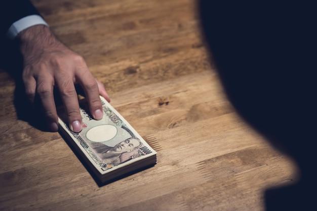 Ein geschäftsmann, der geldbanknoten der japanischen yen in der tat der bestechungskorruption weitergibt