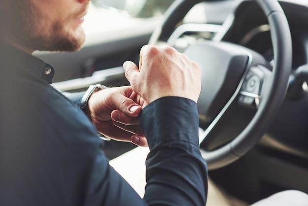 Ein geschäftsmann fährt mit seinem auto und fährt am steuer. hand mit uhr.