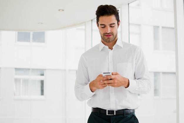 Ein geschäftsmann hält seinen smartphone und sms