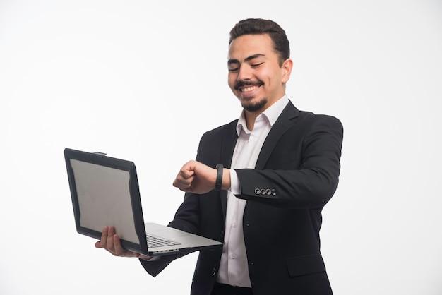 Ein geschäftsmann in der kleiderordnung, der einen laptop hält und zeit zeigt.