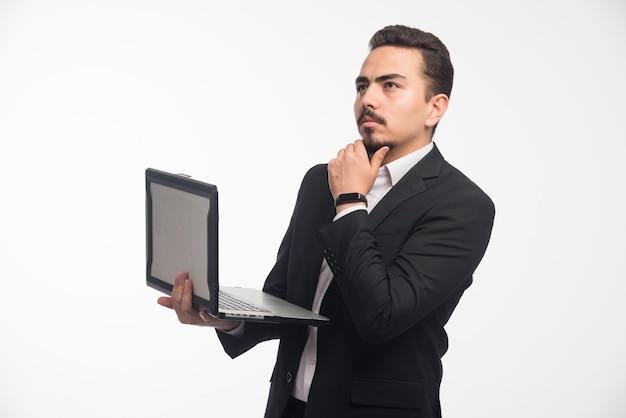 Ein geschäftsmann in der kleiderordnung, die mit einem laptop aufwirft.