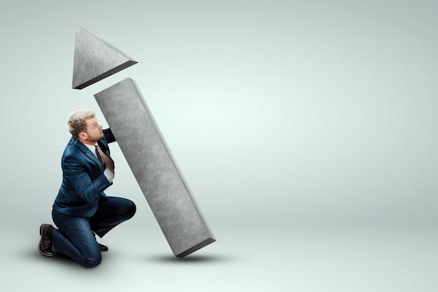 Ein geschäftsmann in einem business-anzug hält, dreht den richtungspfeil
