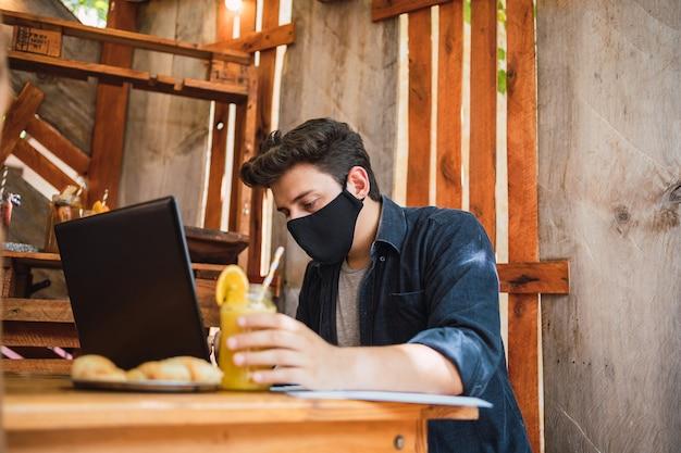Ein geschäftsmann in einer gesichtsmaske, der an seinem laptop an einer bar arbeitet.