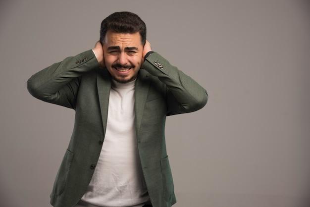 Ein geschäftsmann in kleiderordnung hält sich die ohren zu, als es laut wird.