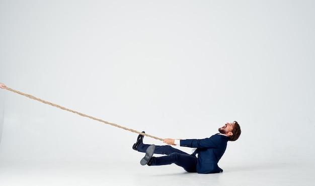 Ein geschäftsmann liegt auf dem boden und zieht ein seil an einem hellen raum drinnen