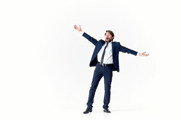 Ein geschäftsmann mit bart in einem klassischen anzug gestikuliert mit den händen auf einer hellen hintergrundkopie