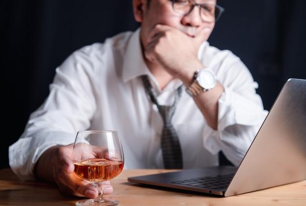 Ein geschäftsmann mit einem whiskyglas wegen des stresses, nachts hart zu arbeiten