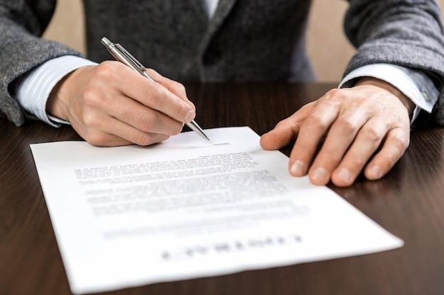 Ein geschäftsmann sitzt an einem schreibtisch und unterschreibt mit einem silbernen kugelschreiber einen vertrag.