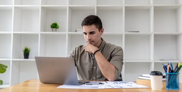 Ein geschäftsmann sitzt in seinem büro mit laptop und schreibwaren, auf seinem schreibtisch liegen finanzdokumente, die er überprüft, er tippt, schreibt sms, spricht über einen laptop-messenger mit seinem partner.