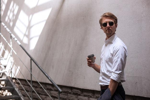 Ein geschäftsmann trinkt kaffee zum mitnehmen, während er in einer pause ist