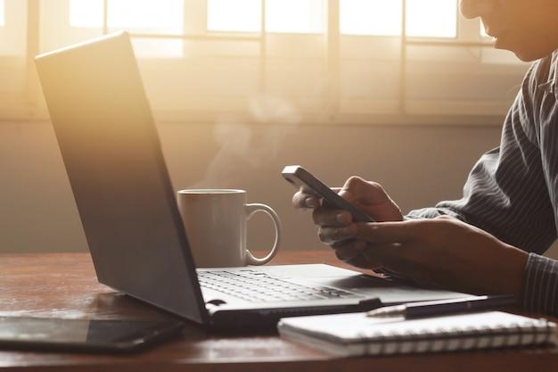 Ein geschäftsmann unter verwendung des smartphone mit laptop für arbeit.