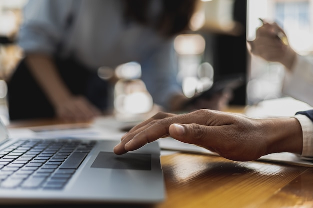 Ein geschäftsmann verwendet einen laptop, um präsentationen anzuzeigen, die atmosphäre eines besprechungsraums eines startup-unternehmens mit führungskräften und vertriebsabteilungen, die ein planungstreffen haben. vertriebsmanagementkonzept.