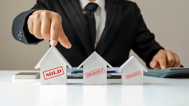 Ein geschäftsmann wählt ein hausmodell mit einer nachricht zum verkauf über immobilienhandelsideen und hypothekendarlehen.