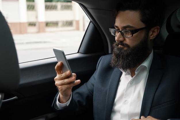 Ein geschäftsmann während der fahrt mit dem auto auf dem rücksitz unter verwendung eines smartphones